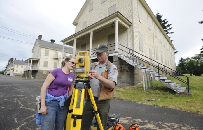Setting up surveying equipment to set up a dig at the site of the 1854 Army flagstaff at Vancouver Barracks