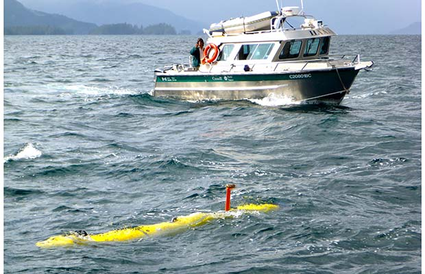 The University of Victoria's Bluefin-12S AUV is shown in Juan Perez Sound with a Gwaii Haanas National Park Reserve vessel in the background in a handout photo. Photograph by: HO-University of Victoria, THE CANADIAN PRESS