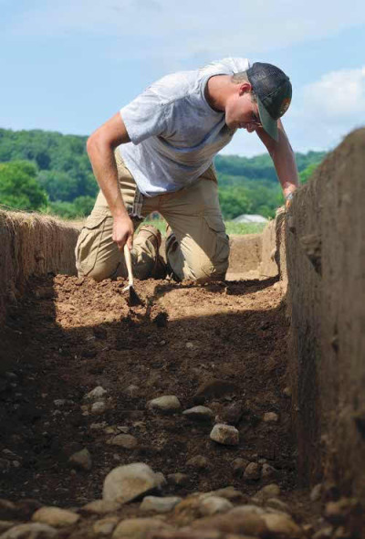 Jarrod Trombley excavates sediments in the ancient ditch that marks the outer edge of the Great Circle.