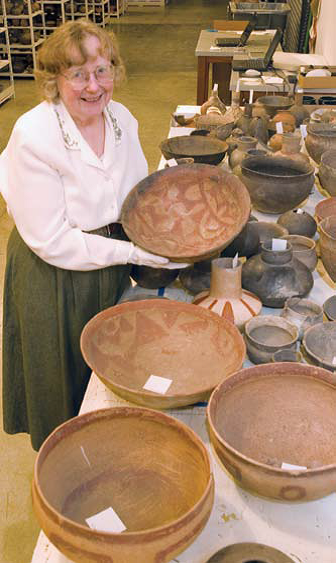 Davis holds a vessel from the collections of the University of Arkansas Museum. Among many other positions she was assistant director of the museum from 1963 to 1967. photo by RICHARD BERQUIST