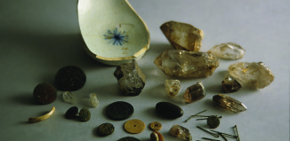 Objects from the Carroll House cache included shell discs, straight pins, buttons, two pierced coins, a tiny faceted glass bead, a smooth black stone, and large rock crystals. The collection was covered with an overturned pearlware bowl. Archaeology in Annapolis/ University of Maryland