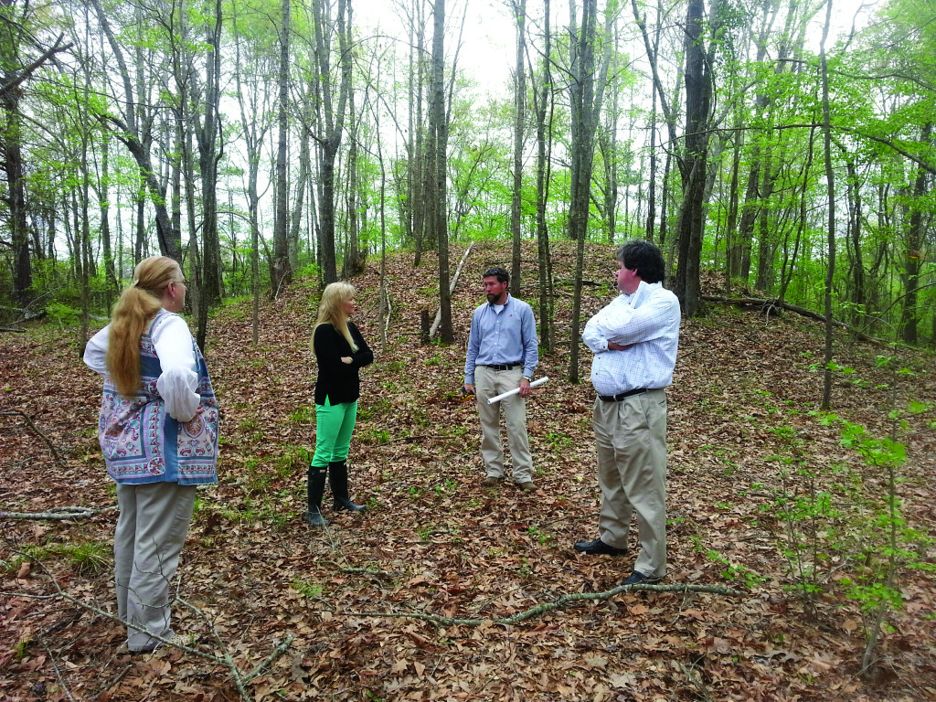 Elizabeth Irwin of the University of Alabama Museums, Jessica Crawford, Southeast regional director for the Conservancy, Matt Gage, director of the Office of the University of Alabama Museums, and Howell Poole, Jr., president of the Bank of Moundville, discuss the significance of the Asphalt Company Mound during a recent site visit.