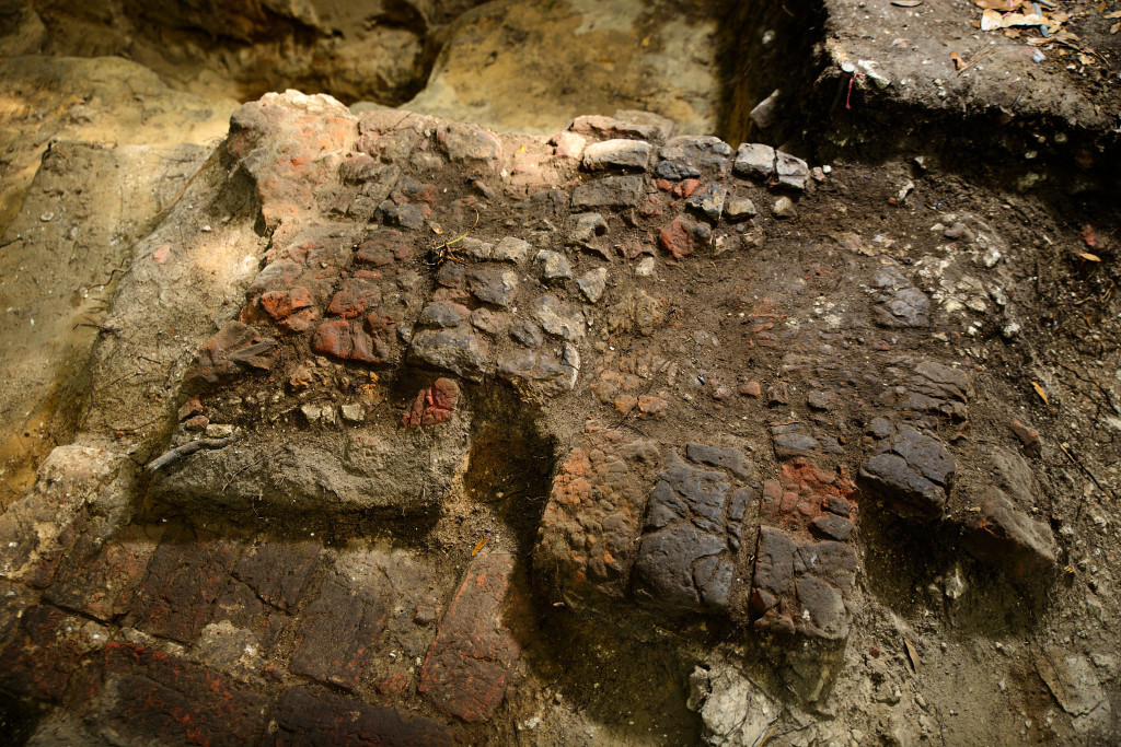 Archaeologists uncovered an intact 1670s brick wall foundation (bottom left) is overlaid by intact brick fireplace hearth (center) at the Miller site. Credit: Patrick Hall