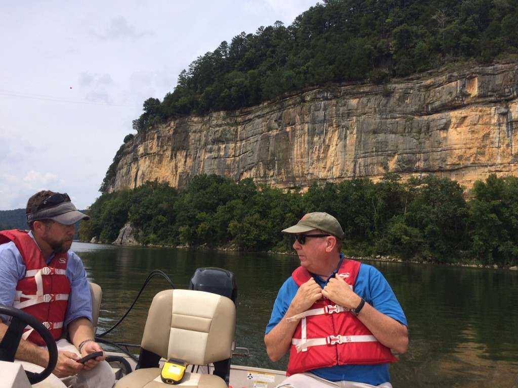 Mark and Matt Gage, Director of the Office of Archaeological Research at The University of Alabama in a boat with Painted Bluff in the background.