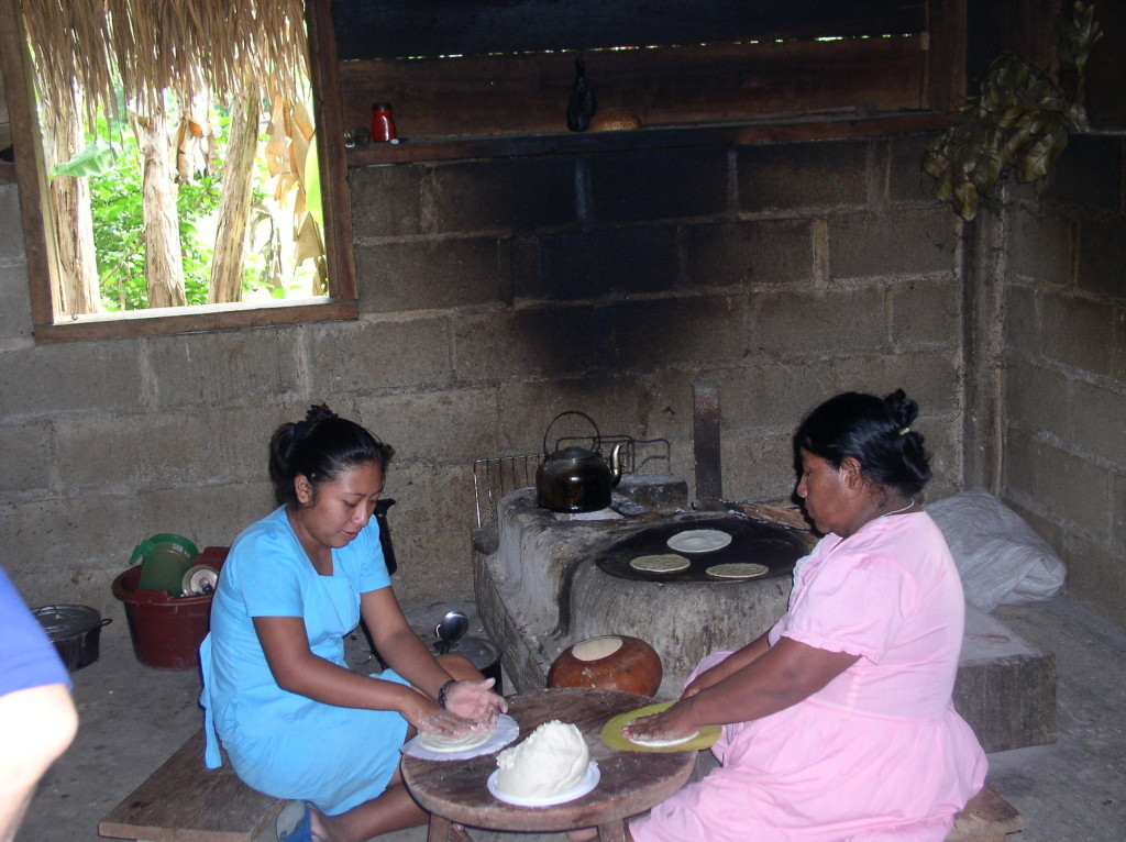Hermenia Valentino (right) makes corn tortillas with one of her daughters. I spent a night in the home of this Maya family to learn about their lives. Credit: Michael Bawaya