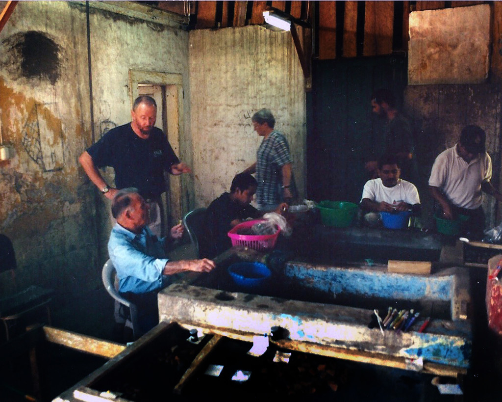 Archaeologist Jonathan Kaplan (standing) instructs members of his crew in a crude laboratory at Chocola. Credit: Michael Bawaya