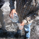Ice Coring Lags - Craig Lee washes off loose material from a core that was extracted from an ice patch. Credit: Jennie Borresen Lee
