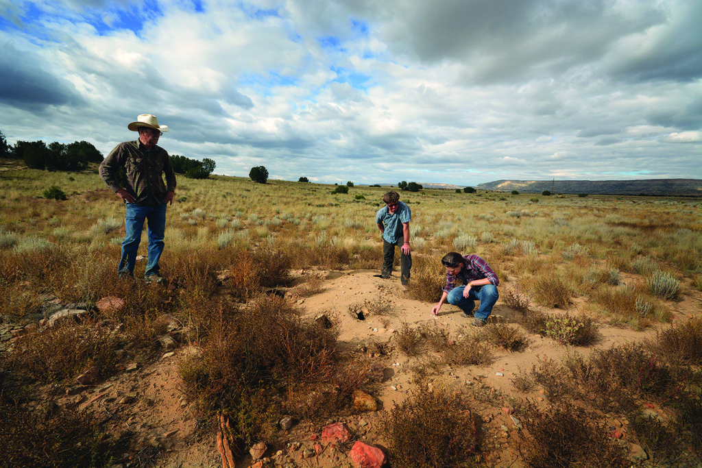 The landowner (left) and Mr. Lawrence (center) look on as Hannah Mattson of the University of New Mexico analyzes ceramics found in a midden at the Conservancy's 500th site. Photo Credit: Chaz Evans