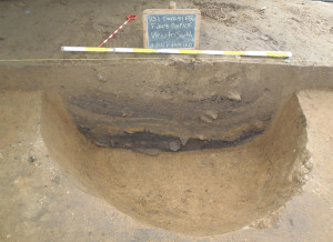 A deep hearth or cooking pit excavated at the Emerald site in 2014. This pit shows evidence of an intense fire that left the charred debris layer at the bottom. The debris was covered with sterile earth (the light brown layer above the black), which appears to be ritualistic. The grey fill midway up the pit profile is silt that could have been placed there by humans, or by nature. Photo credit, Timothy R. Pauketat