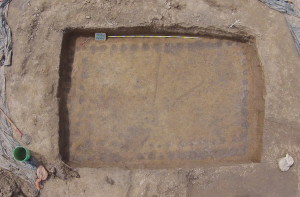 Bird's eye view of a semi-subterranean shrine house floor excavated in 2015 at the Emerald site. The yellow floor plaster is visible against the yellow-brown subsoil around the edges. The dark circles along each of the four walls are post molds. Credit: Jac Lutz.