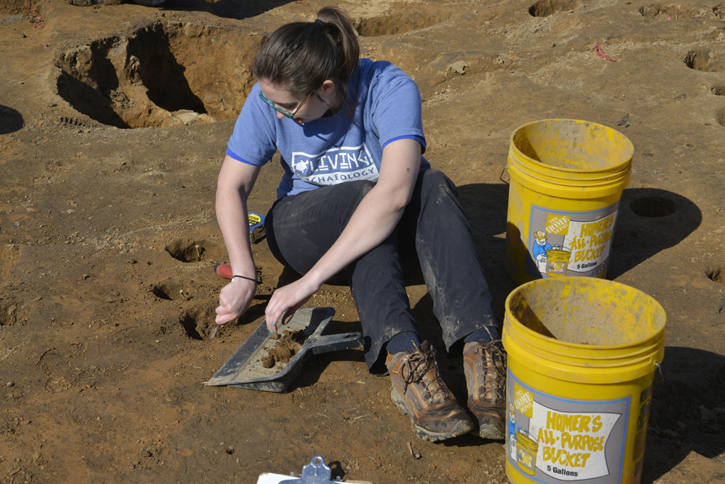 Volunteer Karen Stevens excavates interior postholes associated with a Late Fort Ancient house. Large holes in back of her are the remains of three adjacent pole-pits. These pits held non-structural sacred poles that were repeatedly set and removed. Credit: Art Dickinson