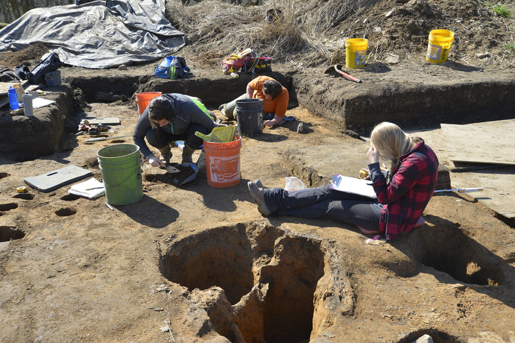 Researchers Katherine Mueller (left) and Thomas Royster (center) excavate the postholes associated with a Late Fort Ancient structure's exterior wall, while Emily Phillips (right) checks her notes. Credit: Art Dickinson