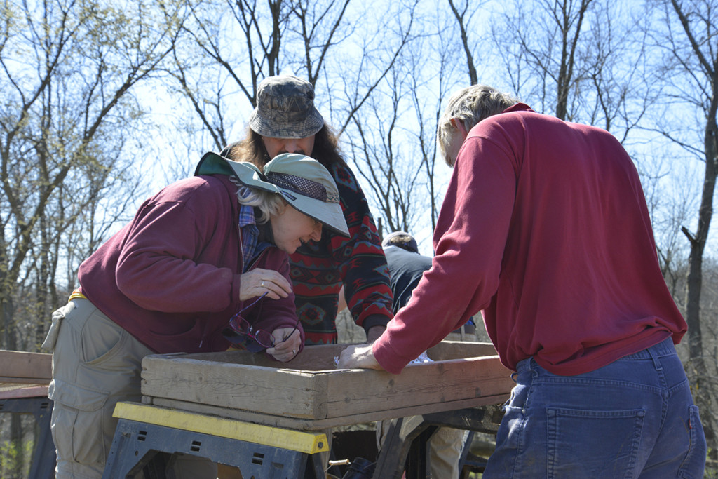 After screening soil from an excavation unit, project director Gwynn Henderson (left), Vince Whitlatch (center) and Ric Matchette examine the screen for any diagnostic artifacts. Credit: Art Dickinson