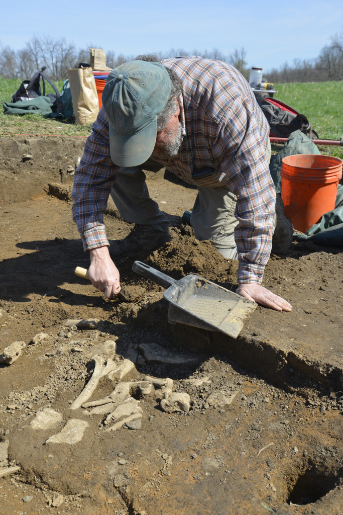 Project director David Pollack excavates a pile of animal bones near the southeast wall of a structure. The bones, which include the remains of at three bears, may represent an offering. Credit: Art Dickinson