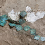 These copper plates were found in situ in 2008. They're thought to be pieces of a necklace. Credit: David Doody