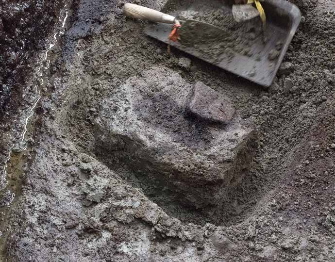 A 13,000-year-old footprint is prepared for removal. The impression, which was made in light colored clay, was subsequently covered by dark sand. Credit: Joanne McSporran / Hakai Institute