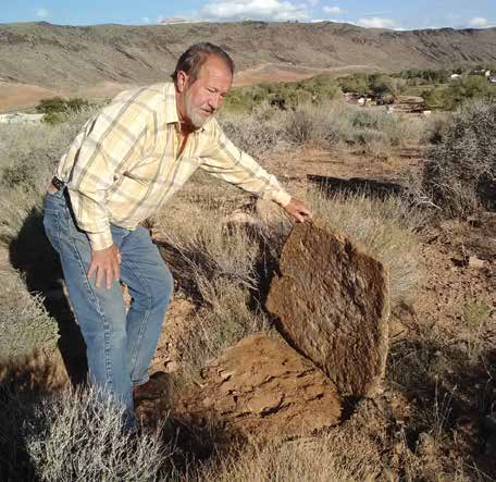 Gaylord Robb holds up a large sandstone slab that could have served as a door for a storage pit or a pit house. Credit: Chaz Evans/ The Archaeological Conservancy.
