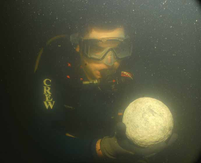 A diver holds a stone cannonball recovered from the Emanuel Point II shipwreck. Photo Credit: UWF Division of Anthropology and Archaeology.