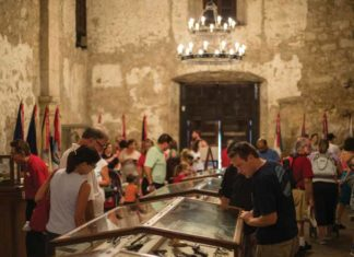 Tourists look at artifacts on display inside the Alamo. Photo Courtesy: Reimagine the Alamo