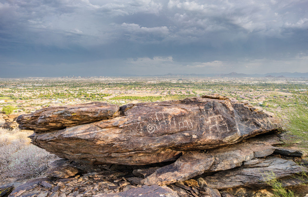 2. The South Mountains rise as an island of darkly hued boulders amid a sea of asphalt and concrete. While thousands of petroglyphs are preserved within the park, their management and stewardship remain constant challenges. Credit: Paul Vanderveen