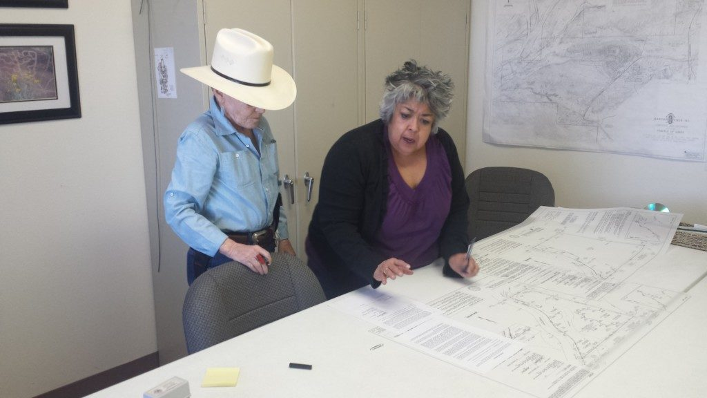 Billie Russell (hat) signing the plat for the Conservancy to acquire Lodestar Ranch, working with Land Title company representative.