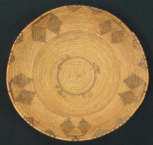 A decorated coiled basket bowl with five butterfly or dragonfly motifs. Credit: @ The Field Museum, Cat. No. 165289/ Laurie Webster