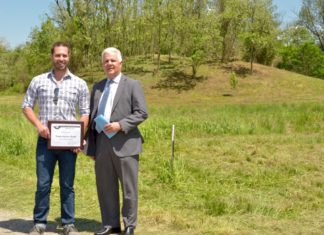 Josh McConaughy, left, celebrates the donation of the Town Square Mound by the Town Square Bank with Bank President Bruce VanHorn