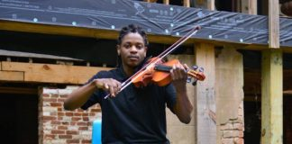 """Musician William Ross, a student in Jackson State University's Classical Music Program, warms up for playing """"Amazing Grace."""" as part of the welcome. (Photo H.P. Lail Photography)"""