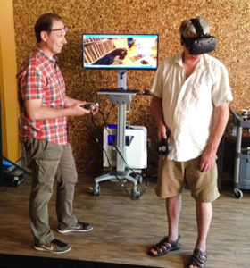 Western Ph.D. student Michael Carter (left) leads a person wearing a virtual reality headset who is immersed in the environment of a sixteenth-century Iroquois longhouse. Credit: Rhonda Bathurst