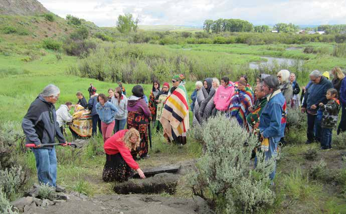 Sarah Anzick (in red jacket) places dirt in the grave of the Clovis-age child who was reburied in a public ceremony. Credit: Michael Waters, Center for the Study of the First Americans.