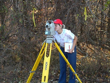 Learning how to use a total station to map coordinates of shovel tests during survey work. Photo Courtesy Kelley Berliner.