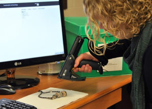 An SA Western employee scans a code that is used to label artifacts. The code correlates with the catalogue number of each artifact that is entered into their online database. Credit: Rhonda Bathurst