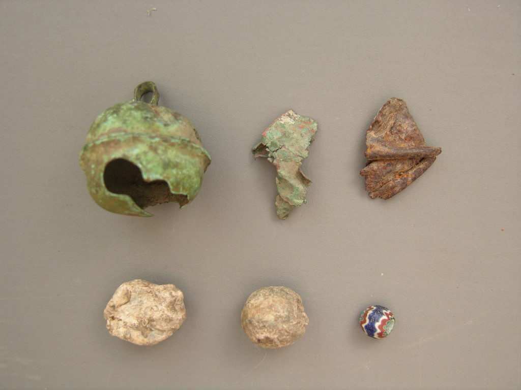 Early sixteenth-century Spanish artifacts from the Parkin site. Top (l to r): Clarksdale bell of brass, Clarksdale bell fragment of brass, Possible Clarksdale bell fragment of bronze. Bottom (l to r): Lead shot that was fired or damaged, Unfired lead shot (.61 caliber), Seven-layer faceted chevron bead. Photo courtesy Arkansas Archeological Survey.