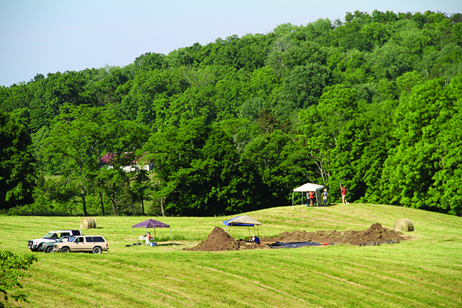 Excavation of Block 1 in foreground and Field team taking transit readings on the mound. 2013. Credit: Carter Robinson Excavation Archives.