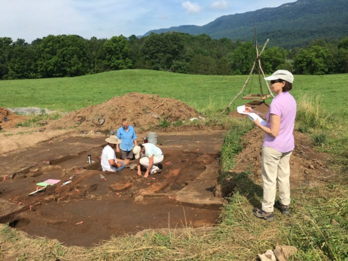 Writer Linda Vaccariello takes notes while Assistant Professor Maureen Meyers shows U of Mississippi undergraduate Conor Foxworth and UM graduate student Emily Warner how to excavate part of the structure wall. The Mound is in the distance. Credit: Charlotte Smith