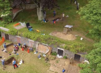 An aerial view of the excavations on Burial Hill. The grey structure with the black and brick doors is an 1830s burial vault that cuts through the site. Excavations in front of and behind the vault revealed a series of building postholes, trash pits, and many seventeenthcentury artifacts from the original settlement. Native American and English pottery was found in the trash pits, suggesting the use of Native pots in the English houses. Credit: Bruce T. Martin.