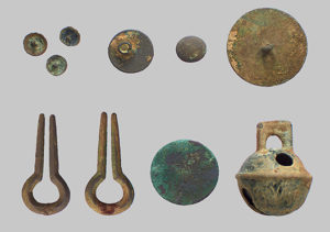 Brass and bronze artifacts—tacks (top left), buttons (top right), Jew's harp frames (bottom left), large cent (bottom center), and bronze sleigh bell (bottom right)—were recovered from New Town:. These artifacts are associated with a cabin believed to be occupied by Catawba leader Sally New River during the early 1800s. Credit Steve Davis.