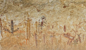 The mural at Halo Shelter is a spectacular example of Pecos River style. Some of its most intriguing figures include a four-foot-tall yellow and red anthropomorph with pincer-like fingers, a feather headdress, and a long staff. Just below and to the right of this figure is an antlered red and black anthropomorph. The red antlers are tipped in black dots. And, like so many other similar figures, the black dots were painted before the red antlers. Credit: Photo courtesy of Shumla Archaeological Research and Education Center.