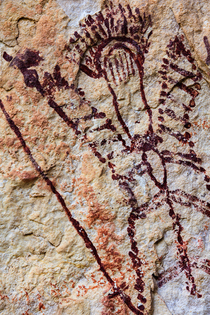 "This finely executed anthropomorph is portrayed with a headdress and vertical lines across its forehead, possibly representing tattoos. Natural features in the rock wall were incorporated into the painting to represent eyes. This practice of ""incorporation"" was common among Pecos River style artists. Credit: Photo by Jerod Roberts, courtesy of Shumla Archaeological Research and Education Center"