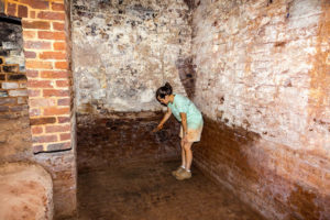 Archaeologist Crystal Ptacek stands on the recently uncovered brick floor of Monticello's original kitchen, in the basement of the South Pavilion. She is pointing to the thermally fractured bricks that mark the location of the original kitchen fireplace that was dismantled around 1809, when a new kitchen was completed closer to Jefferson's mansion. Credit: Mark East.