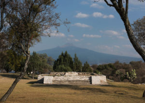 The platform of a temple is seen here. The Malinche volcano towers in the background. Credit: Adam Wiseman