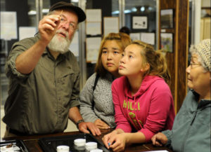 Nunalleq project director Rick Knecht shows an amber bead to Quinhagak residents attending the show and tell in 2014. credit: Erik Hill, Alaska Dispatch News