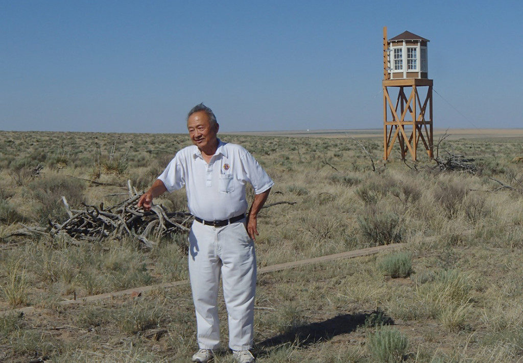 Another former Amache internee points to the place where his former barracks once stood. A reconstructed guard tower stands in the background. Credit: Denver University's Amache Project