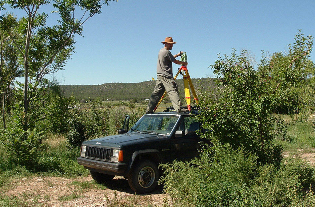 Jun Sunseri stands on the hood of a truck while surveying a site in El Rito, in northern New Mexico. Credit: Charlotte Sunseri