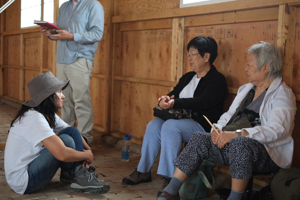 A high school intern talks with two former Amache internees in the barracks. The barracks are a historically-accurate reconstruction of the original structure in which the two women were once confined. Credit: Greg Kitajima