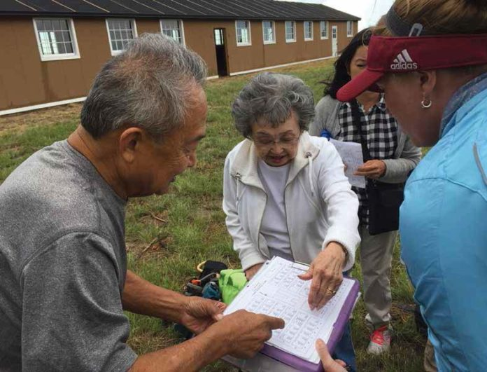 Tooru Nakahira (left) and Anna Shishido (center), two former internees at Amache, point to a diagram of the barracks where they were once confined. The barracks have been reconstructed (background) based on historical and archaeological evidence. Credit: Nancy Ukai