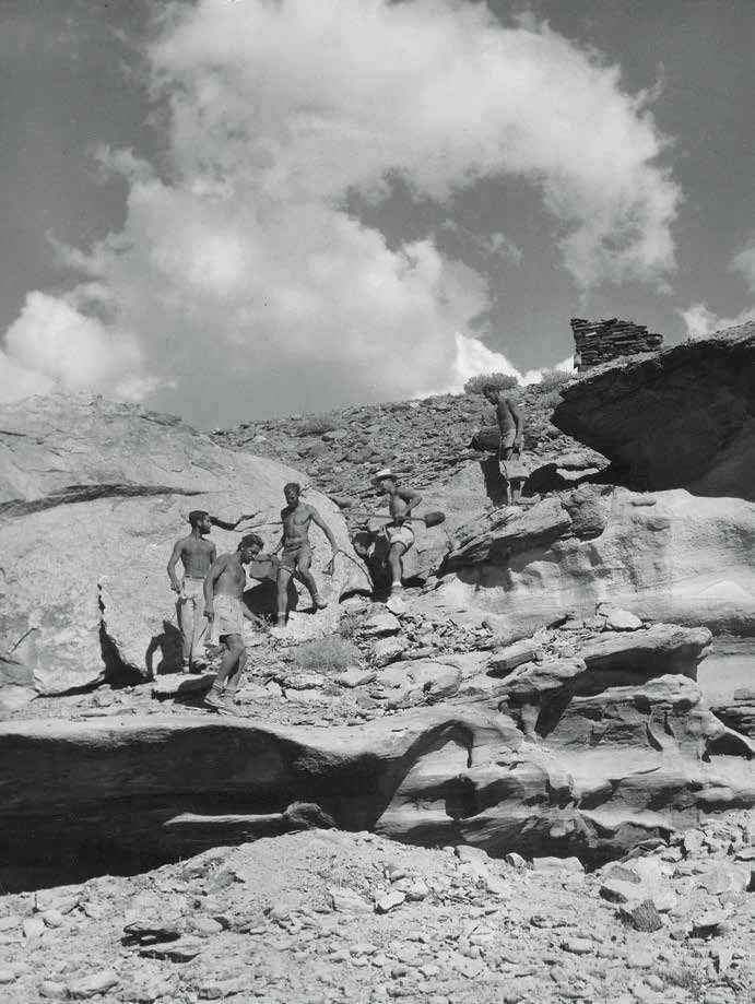 An excavation crew descends ledges below Loper Ruin during work on the Glen Canyon Project in August, 1958. Bill Lipe is in the middle carrying a camera case. Loper, a 13th-century habitation site, was submerged by the formation of Lake Powell. Courtesy of Natural History Museum of Utah.