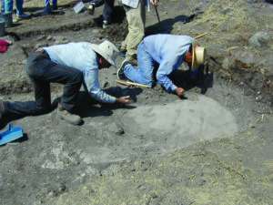 Researchers uncover a plaster floor of a terrace at El Palmillo in the Oaxaca Valley of Mexico. The researchers believe that the size of a terrace is an indication of the size of a house, and size of a house was an indication of its resident's wealth. Credit: Linda Nicholas