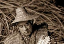 Ed Carriere weaves a cattail basket. He also wove the cedar-bark vest and cedar-bark hat he's wearing. Credit: FREDRICK DENT