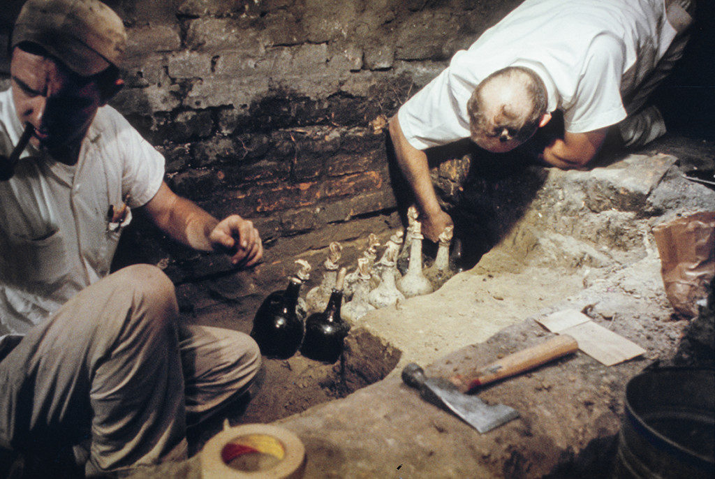 Ivor Noël Hume (right), Colonial Williamsburg's first full-time trained archaeologist, excavates a cache of English wine bottles from Wetherburn's Tavern in 1964-5. The bottles were among 200,000 artifacts excavated from the property. Credit: Colonial Williamsburg Foundation.